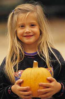 Girl holding pumpkin at Baxter Barn